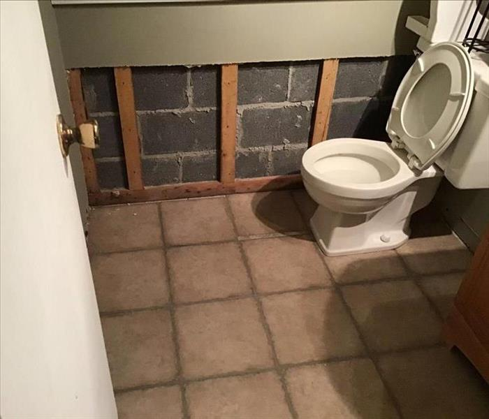 drywall removed from bottom of the wall to expose concrete block in restroom