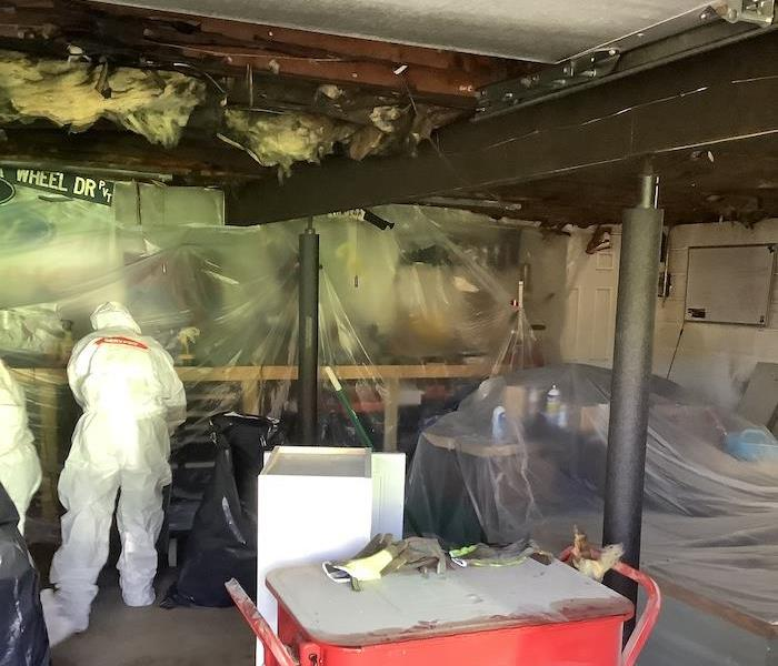 SERVPRO technicians cleaning up fire damage in a garage