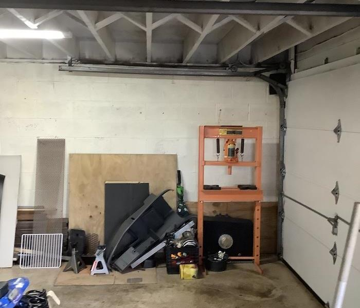 Garage with clean walls and flooring with items stored neatly