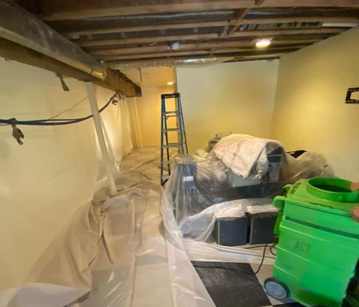 Basement with commercial mold damage and plastic barriers with SERVPRO equipment