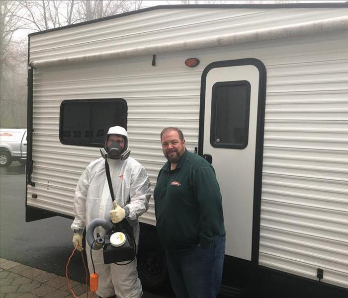 two SERVPRO persons, one in PPE, standing in front of a white travel trailer.