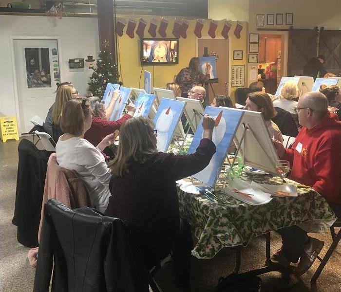 several people sitting around a table painting canvasses