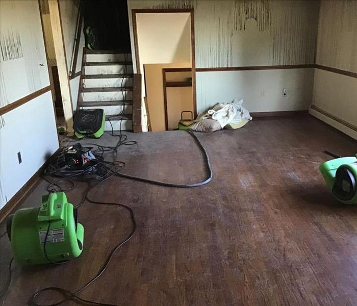 Room with hardwood floors and SERVPRO drying equipment