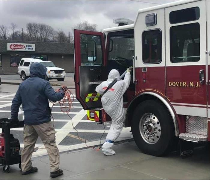 male employee in protective covering stepping into a firetruck