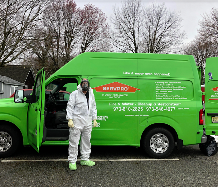 SERVPRO worker standing in front of a SERVPRO truck