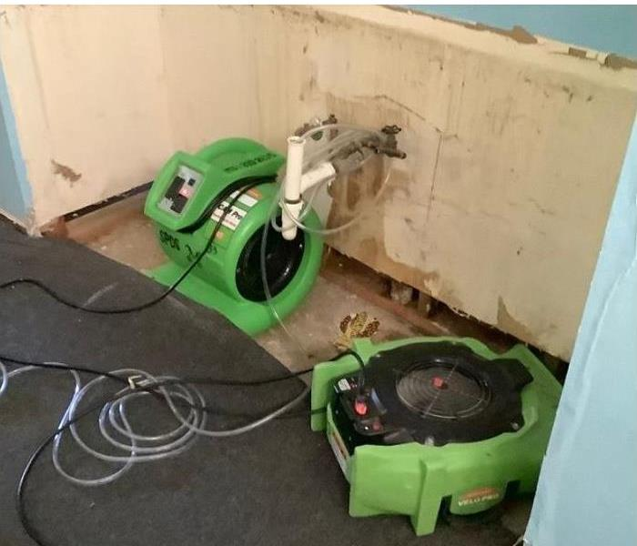 SERVPRO drying equipment in corner of water damaged room