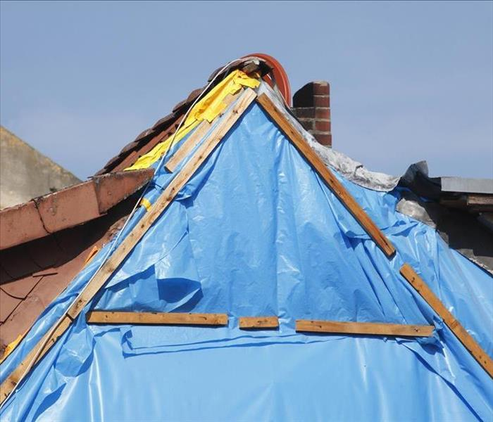 blue tarp on gable of roof